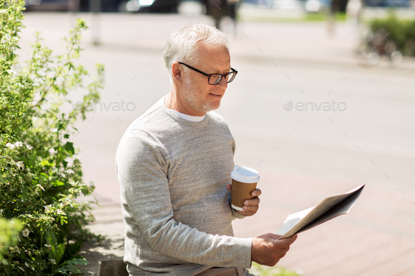 senior man reading newspaper and drinking coffee - Stock Photo - Images