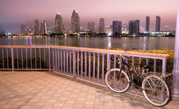 A bike is locked to the fence in Coronado with San Diego in the background - Stock Photo - Images
