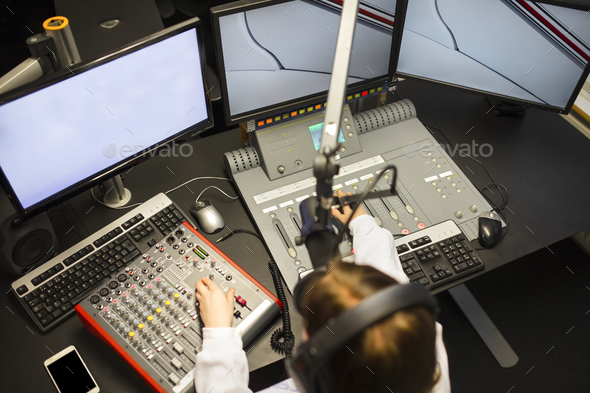 Female Jockey Using Music Mixers And Screens In Radio Studio - Stock Photo - Images