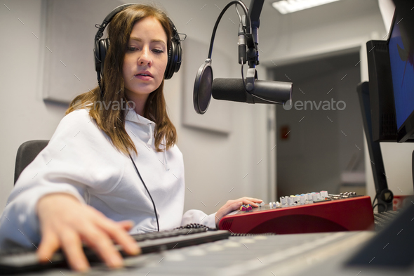 Focsued Radio Host Wearing Headphones In Studio - Stock Photo - Images