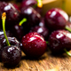 Berries of a sweet cherry in a wooden plate on a background of boards - PhotoDune Item for Sale