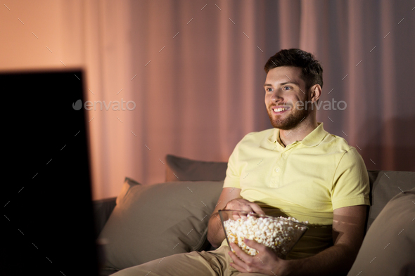 happy man with popcorn watching tv at night - Stock Photo - Images