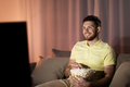 happy man with popcorn watching tv at night - PhotoDune Item for Sale