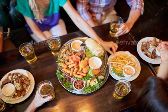 friends eating and drinking at bar or pub - Stock Photo - Images