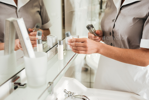 Young hotel maid putting bath accessories in a bathroom - Stock Photo - Images