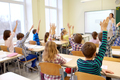group of school kids raising hands in classroom - PhotoDune Item for Sale