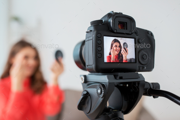 woman with eyebrow pencil recording video at home - Stock Photo - Images