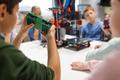 kids with 3d printer part at robotics school