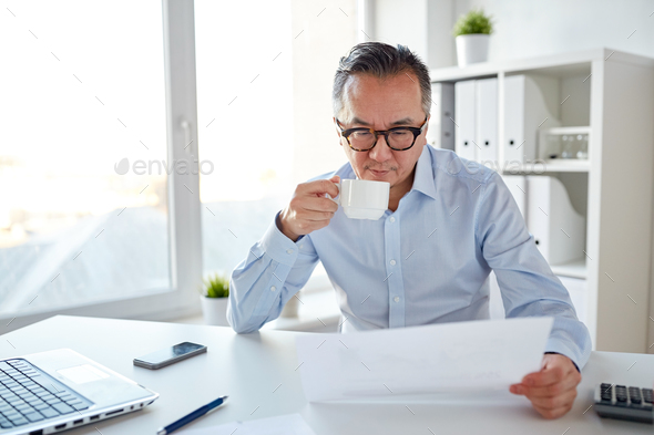 businessman with papers drinking coffee at office - Stock Photo - Images