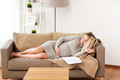 happy pregnant woman sleeping on sofa at home