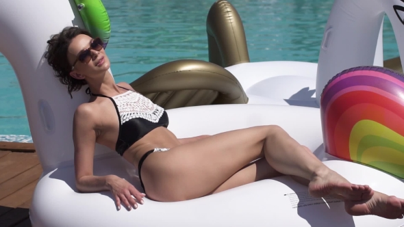 Young Woman in Swimsuit Sunbathing Lying on an Inflatable Mattress a Unicorn