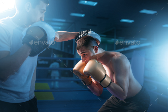 Boxer in gloves exercises with sparring partner - Stock Photo - Images