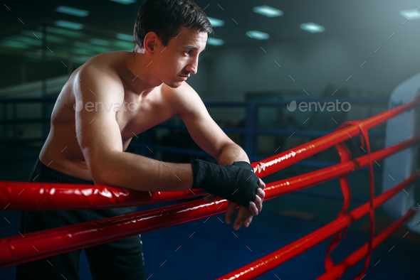Boxer in black bandages poses on ring ropes - Stock Photo - Images