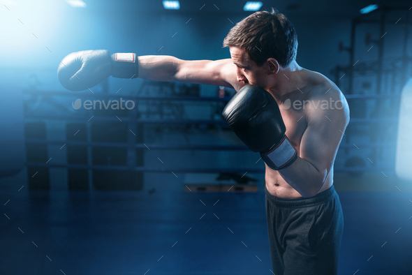 Muscular boxer in black gloves training in gym - Stock Photo - Images
