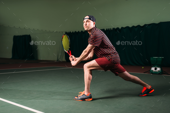 Man with tennis racket playing on indoor court - Stock Photo - Images