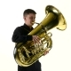 Man Plays on the Tuba Slow Melody. White Studio Background