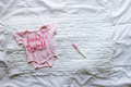 Newborn baby girl clothes and pregnancy test on white background