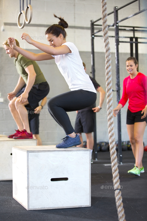 Determined Athletes Doing Box Jumping In Health Club - Stock Photo - Images