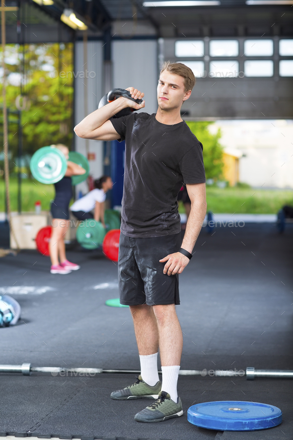 Confident Athlete Carrying Kettlebell In Health Club - Stock Photo - Images