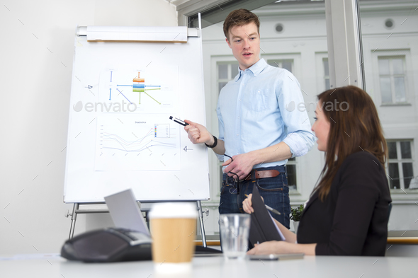 Confident Businessman Giving Presentation To Colleague In Office - Stock Photo - Images