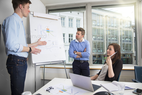 Young Businessman Explaining Chart To Male And Female Coworkers - Stock Photo - Images