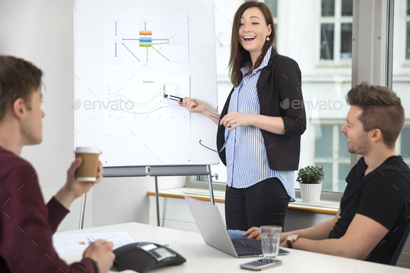 Businesswoman Laughing While Giving Presentation To Male Colleag - Stock Photo - Images