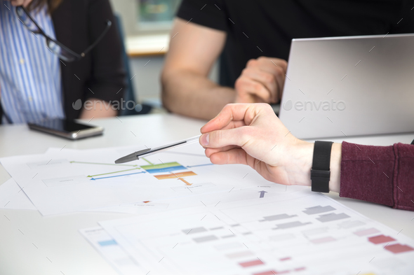 Businessman's Hand Pointing On Chart On Desk - Stock Photo - Images