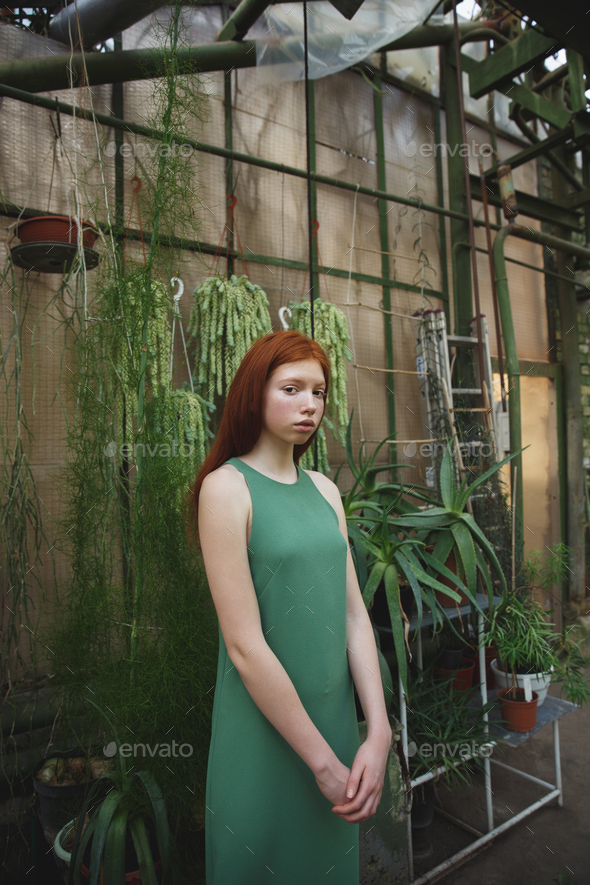 Portrait a young redheaded woman in dress standing - Stock Photo - Images