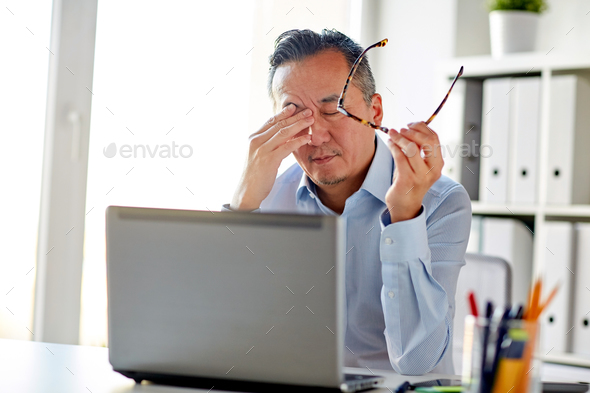 tired businessman with glasses at laptop in office - Stock Photo - Images