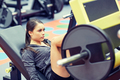 woman flexing muscles on leg press machine in gym