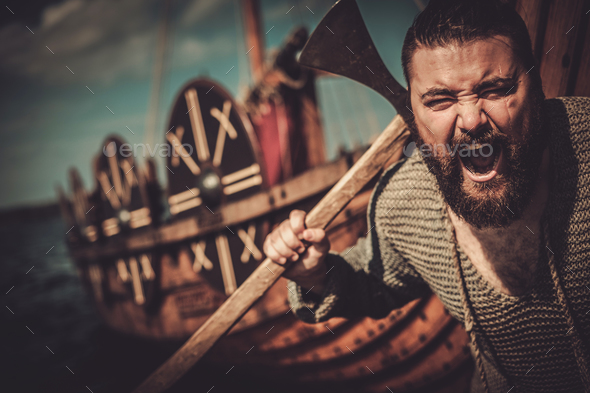 Viking with axe standing near drakkar on the seashore. - Stock Photo - Images