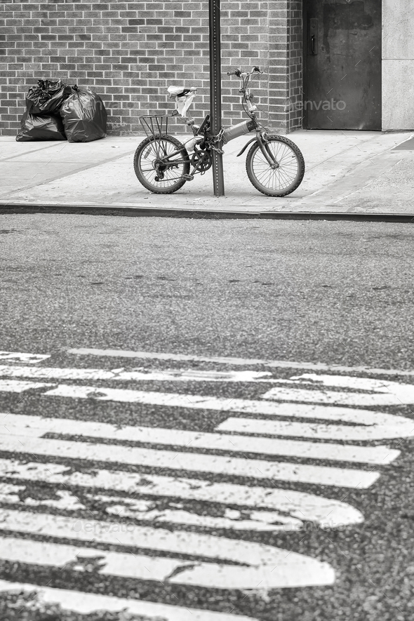 An old bicycle locked to a sign post in Chinatown, NYC, USA. - Stock Photo - Images