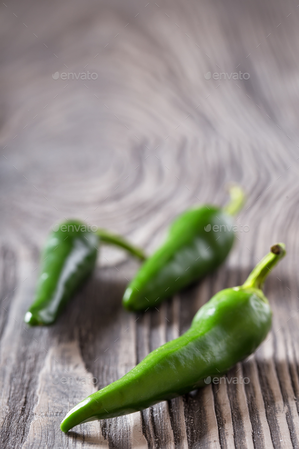 Three green hot peppers on a wooden table - Stock Photo - Images