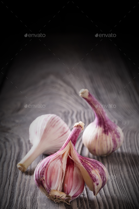 Broken garlic head on a wooden table - Stock Photo - Images