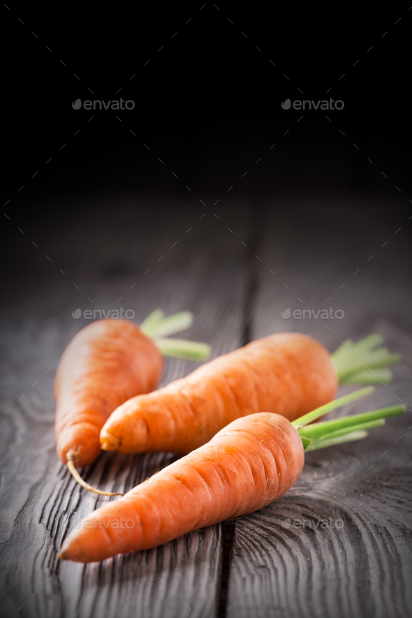 Three bright juicy carrots on a wooden table - Stock Photo - Images