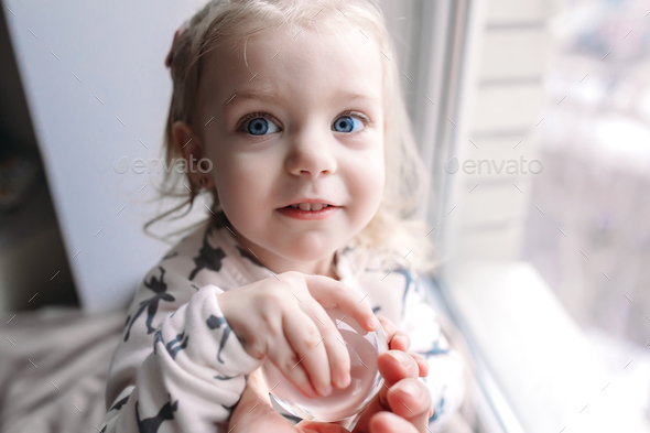 Little girl sitting near the window - Stock Photo - Images