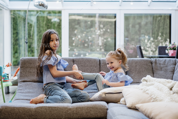 two sisters playing together on the big couch - Stock Photo - Images
