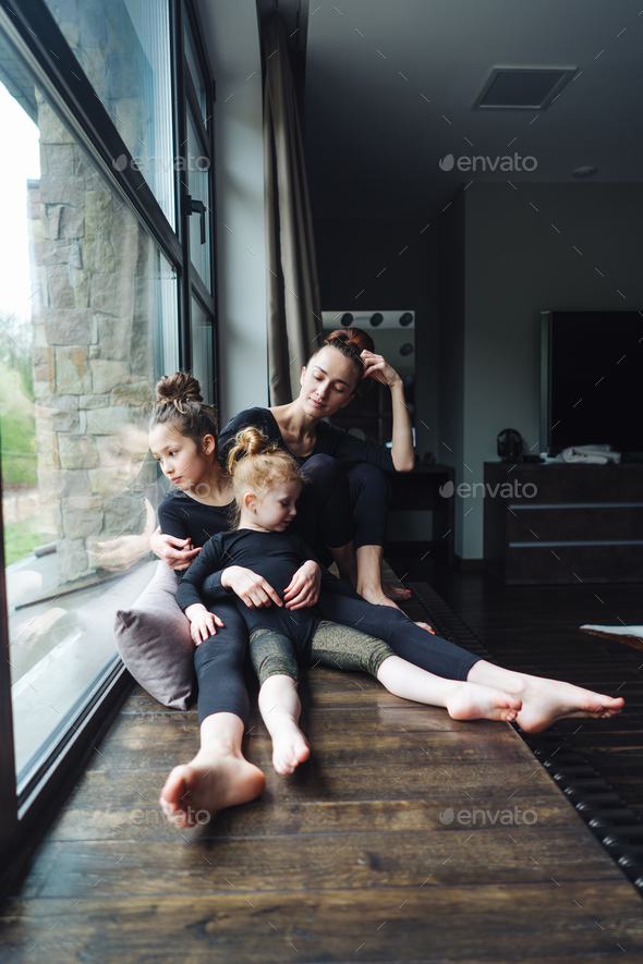 Mom and two daughters together at the window - Stock Photo - Images