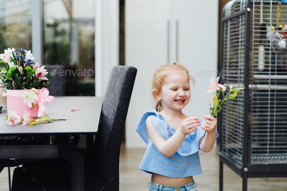 Little girl puts flowers on table - Stock Photo - Images