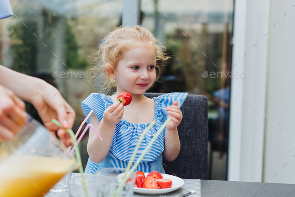 Little girl eating fresh strawberries - Stock Photo - Images