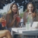 Stylish Young Girls Having Drinks Outside