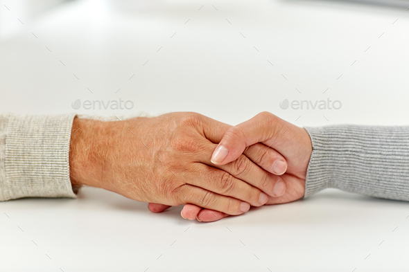 close up of old man and young woman holding hands - Stock Photo - Images