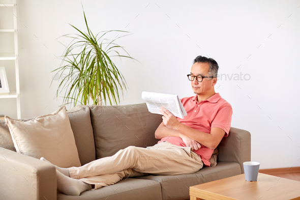 happy man in glasses reading newspaper at home - Stock Photo - Images
