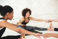 Happy multiethnic people in yoga studio stretching.