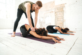 Male yoga instructor helping woman to stretch - PhotoDune Item for Sale
