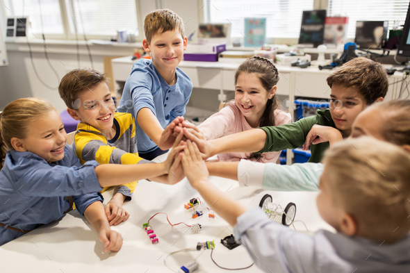 happy children making high five at robotics school - Stock Photo - Images