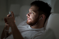 man with smartphone and earphones in bed at night - PhotoDune Item for Sale