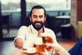 man clinking beer glass with friends at restaurant - PhotoDune Item for Sale