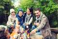 happy family roasting marshmallow over campfire - PhotoDune Item for Sale