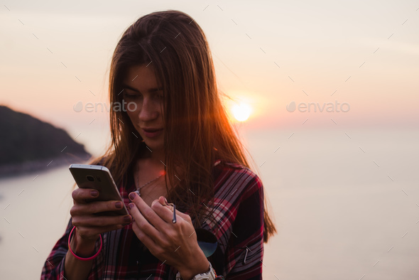 Girl using cellphone near the sea in sunrise or sunset. - Stock Photo - Images